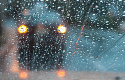 Broken Down. Through the glass shot of a broken down car in the rain featuring rain drops and foggy glass. Car has hazard lights flashing royalty free stock images