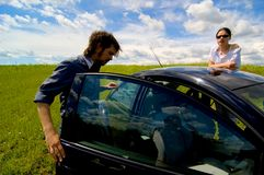 Broken Down 3. Man and woman on outside of a stranded car with doors open in the middle of a field Stock Photography