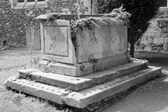 Broken down altar tomb in Black and White. A broken and decaying altar-tomb (gravestone), with ivy growing out of the top located in an English churchyard stock photos
