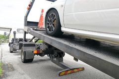 Car towed onto flatbed tow truck with hook and chain. Broken down auto vehicle car towed onto flatbed tow truck with hook and chain stock photo