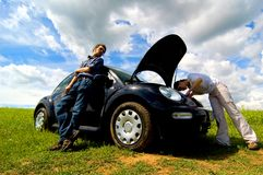 Broken Down Car. Two people stuck in a field with a broken down car royalty free stock photos