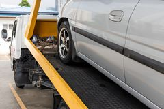 Broken down car towed onto flatbed tow truck with hook cable. Broken down car being towed onto flatbed tow truck with cable for repair at workshop garage stock photography