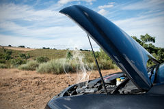 Broken Down Car. Close up of a broken down car, engine open with smoke, in a rural area Stock Images