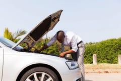 Broken down car engine. Afro american man looking at broken down car engine by side of the road Royalty Free Stock Photos