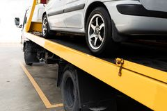 Broken car on flatbed tow truck being transported for repair. Broken down car on flatbed tow truck being transported to garage workshop for repair royalty free stock images