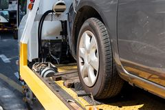 Broken car on flatbed tow truck being transported for repair. Broken down car on flatbed tow truck being transported to garage workshop for repair royalty free stock image