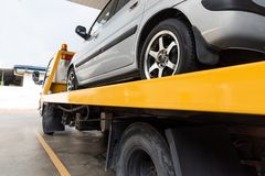 Broken car on flatbed tow truck being transported for repair. Broken down car on flatbed tow truck being transported to garage workshop for repair royalty free stock photography