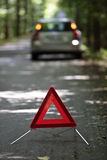 Broken down car on a forest road. Broken down car with warning triangle behind it waiting for assistance to arrive (shallow depth of field, the focus is on the Royalty Free Stock Photos
