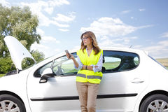 Broken down car on the road. Portrait of confident woman wearing high visibility safety vest while standing on the road alongside her broken down car and using Royalty Free Stock Photos