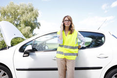 Broken down car on the road. Portrait of confident woman wearing high visibility safety vest while standing on the road alongside her broken down car and using Stock Photos