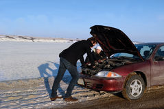 Broken Down Car on Side of Road. A stranded couple with broken down car on side of the road in winter Royalty Free Stock Images