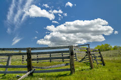 Broken down corral in a field with clouds Stock Photo