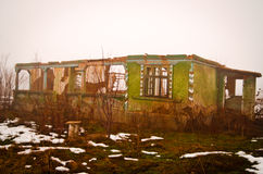 Broken down home in the middle of nowhere. A broken down home/building during a winter day, foggy and washed out; with an orange vibe in saturation Royalty Free Stock Images
