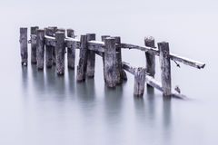 Broken down old pier posts in calm water, covered with light dus. Ting of snow Royalty Free Stock Photo