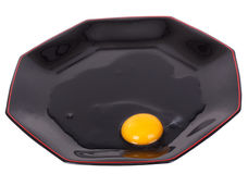 Broken egg on the black plate Royalty Free Stock Photography