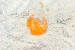 Broken egg on flour Stock Photo