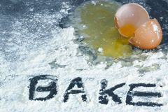 A broken egg on a surface covered in flour with the word Royalty Free Stock Images