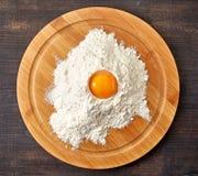 Broken egg in flour on cutting board Stock Photos