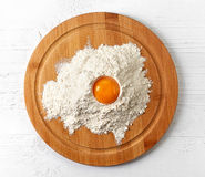 Broken egg in flour on cutting board Stock Image
