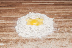 Broken egg on flour Royalty Free Stock Image