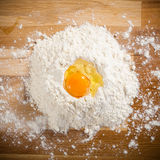 Broken egg on flour, means for making bread Royalty Free Stock Photo