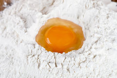 Broken egg on flour Stock Photos