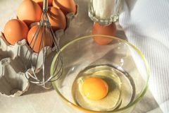 Broken egg in a glass bowl ready for whipping. Fresh chicken egg. S in a cardboard tray, whisk and white towel on a kitchen table Royalty Free Stock Images