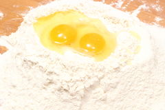 Broken egg in heap of flour lying on table Stock Photo