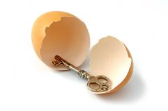 Broken egg and key Stock Images