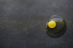 Raw yolk on dark table in the kitchen.Broken egg stock photos