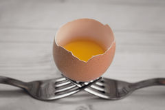 Broken egg rests on two forks Stock Photography