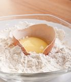 Broken egg with shell on flour Royalty Free Stock Image
