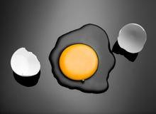 Broken egg. Shell with yolk and albumen on black stock image