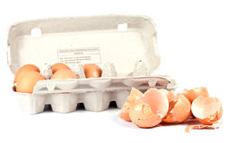 Broken egg shells and whole eggs on white Royalty Free Stock Images