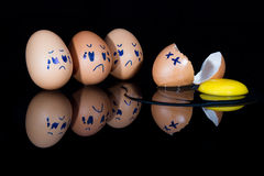 Broken egg on shiny black surface with friends being sad Stock Image
