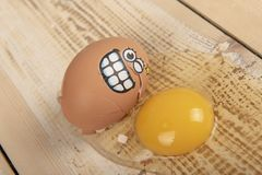 Broken egg with smiley face. On wooden background royalty free stock images