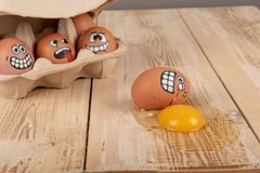 Broken egg with smiley face. On wooden worktop royalty free stock photo