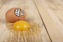Broken egg with smiley face. On wooden work top stock images