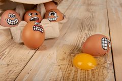 Broken egg with smiley face. On wooden work top stock image