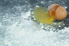 A broken egg on a surface covered in flour Royalty Free Stock Photography