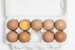 The A broken egg among whole eggs in an egg carton. A broken egg among whole eggs in an egg carton Stock Image