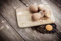 Broken egg on a wooden cutting board on wooden Royalty Free Stock Image