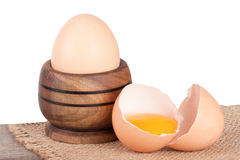 Broken egg with yolk and eggshell on a wooden table with a white background.  Stock Photos