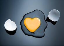 Broken egg and yolk. Broken egg and yolk with heart shaped yolk royalty free stock photo