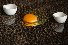 Broken egg with yolk, protein and shell on leopard skin. With reflection royalty free stock images