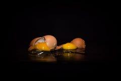 Broken eggs. In black background royalty free stock photos