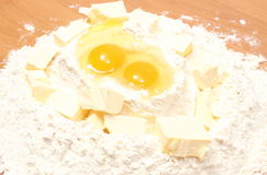 Broken eggs in flour and cube of margarine lying on table Royalty Free Stock Photos