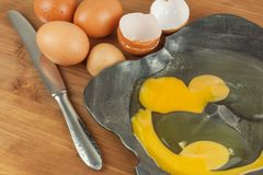 Broken eggs on forged metal bowl. Domestic eggs on a wooden table. Source of quality protein. Metal bowl of raw eggs and egg shell Royalty Free Stock Image