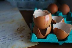 Broken eggs after making a cake and a recipe stock images