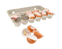 Broken eggs plus egg carton. A group of broken and used eggs in the foreground with the remainder in a cardboard carton in the background Stock Photos